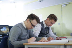 Two male Post 16 Longfield Academy students sit together whilst writing on paper with pens.